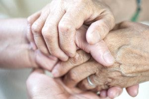 Close up of two people clasping hands.