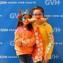 Two children, one wearing oversized heart-shaped sunglasses and a bow headband, and one wearing fake glasses and red ball nose with a large mustache and an oversized orange polka dot tie - in front of blue GVH wall background at Heart Fair.