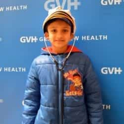 Child wearing a sailor hat - in front of blue GVH wall background at Heart Fair.