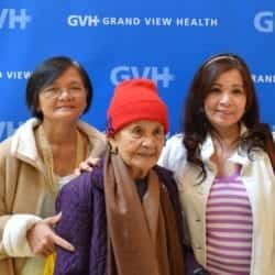 Three adults of different generations - in front of blue GVH wall background at Heart Fair.