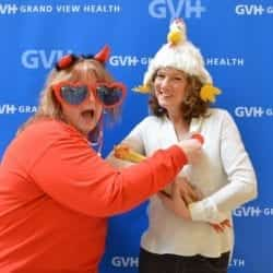 Two adults, one wearing a pair of oversized heart-shaped sunglasses and devil horns, the other wearing a chicken hat - in front of blue GVH wall background at Heart Fair.