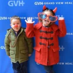 Two children, one with red ball nose and one wearing oversized heart-shaped sunglasses and devil horns - in front of blue GVH wall background at Heart Fair.