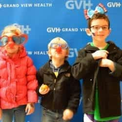 Three children, one wearing oversized heart-shaped sunglasses, one wearing a red ball nose and one wearing a bow headband - in front of blue GVH wall background at Heart Fair.
