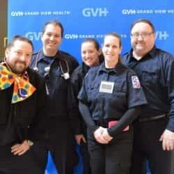 Five adults in medical attire and one with an oversized polka dot bowtie - in front of blue GVH wall background at Heart Fair.