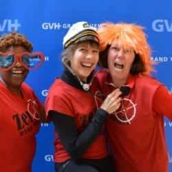 Three women, one with oversized heart-shaped sunglasses, one with a sailor hat, and one with an orange wig - in front of blue GVH wall background at Heart Fair.