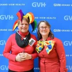 Two adults, one wearing a jester hat and the other wearing an oversized polka dot bowtie - in front of blue GVH wall background at Heart Fair.