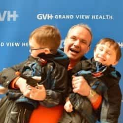 Man and two children - in front of blue GVH wall background at Heart Fair.