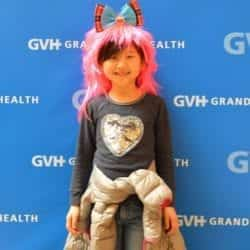 Child wearing a pink wig and bow headband - in front of blue GVH wall background at Heart Fair.