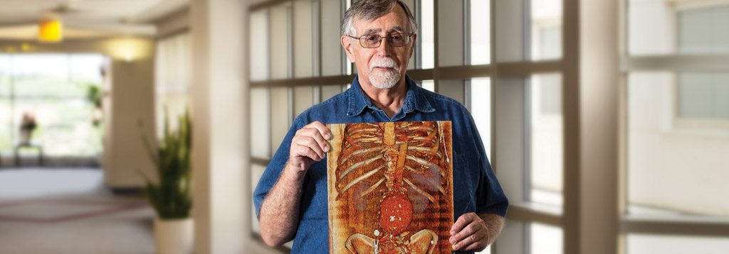 John Defeo standing in hospital hallway, holding up an illustrated image of a skeleton and stomach.
