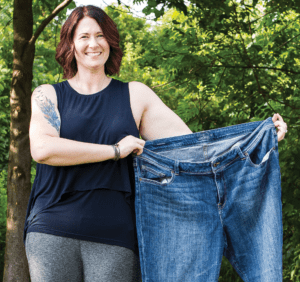 Woman holding up pair of large jeans.