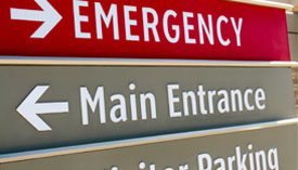 Close-up of map sign, EMERGENCY pointing right and Main Entrance pointing left.