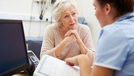 Patient listens intently as medical professional reads information from a form.